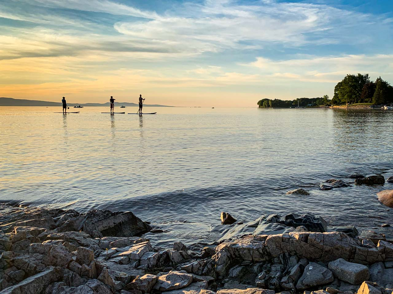 three paddle boarder on the water as the sun begins to set rocks in foreground