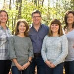 a portrait of a dentist and his team of dental assistants photographed in woods