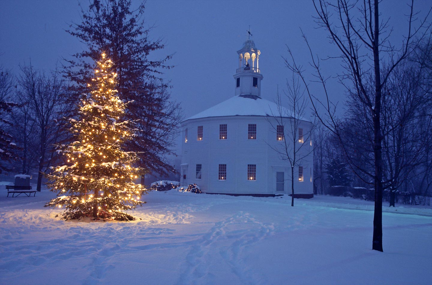 the old round church with lights in the windows and lit tree in front in the blue color of dusk