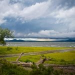 dark clouds over white capped water and mountains driftwood and tree in foreground