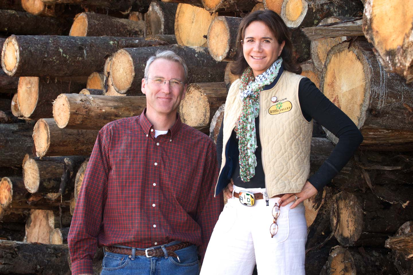 smiling couple in front of logs