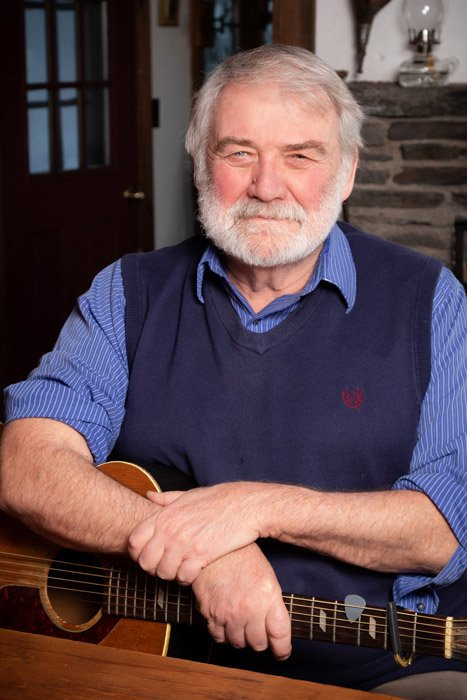 grey haired bearded man in blue shirt and vest holding his guitar