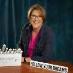 woman in front of blue studio background smiling and looking at camera and sitting at desk in front of her are decorative signs saying believe, you can, follow your dreams.