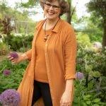 women in orange standing in a garden of purple allium flowers used for business web site