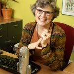 woman sitting in her office desk behind her computer with podcast microphone in front of her smile on her fact